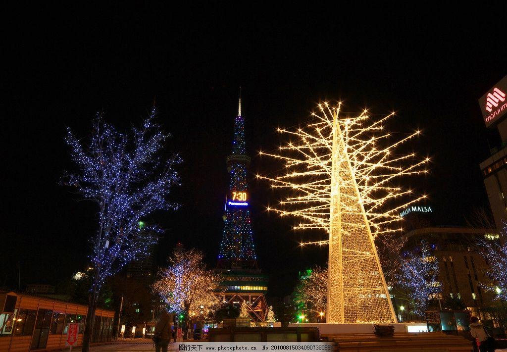 圣诞节灯饰 夜晚 塔形建筑 圣诞树 彩灯 树木 游人 房屋 假日游玩