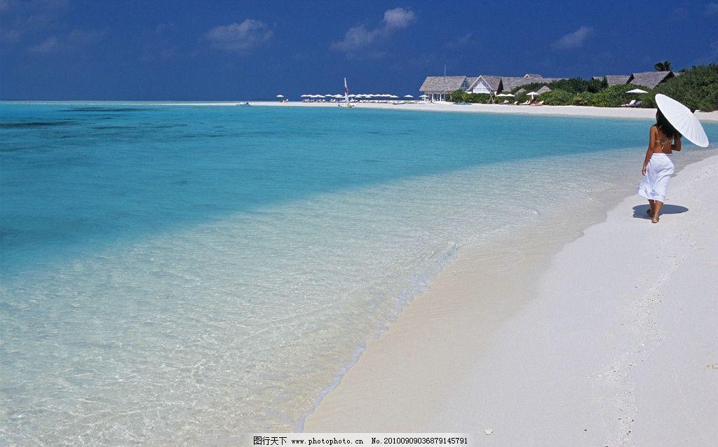 美女带着太阳伞在海边沙滩上散步图片